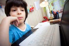Aprendizaje a distancia, niño preescolar con el ordenador Fotos de archivo