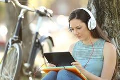 Aprendizaje electrónico del estudiante con la tableta y los auriculares Fotos de archivo