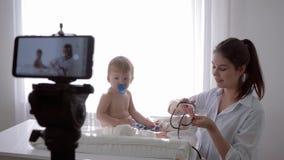 Aprendizaje electrónico, muchacha del doctor con los controles del estetoscopio al latido del corazón y respiración del bebé paci almacen de metraje de vídeo