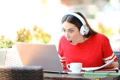 Aprendizaje electr?nico sorprendente del estudiante en una cafeter?a foto de archivo