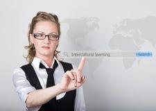Aprendizaje intercultural escrito en barra de la búsqueda en la pantalla virtual Tecnologías de Internet en negocio y hogar Mujer Imagen de archivo libre de regalías