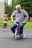 Aprendizaje montar una bici con las ruedas de entrenamiento Fotografía de archivo libre de regalías