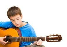 Aprendizaje tocar la guitarra acústica Imagenes de archivo