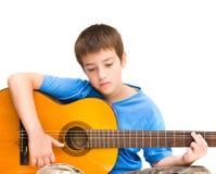 Aprendizaje tocar la guitarra acústica Imágenes de archivo libres de regalías