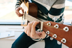 Aprendizaje tocar la guitarra Educación de la música Foto de archivo libre de regalías