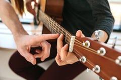 Aprendizaje tocar la guitarra Educación de la música Imágenes de archivo libres de regalías