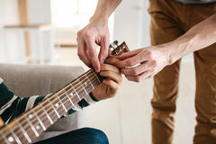 Aprendizaje tocar la guitarra Educación de la música Foto de archivo