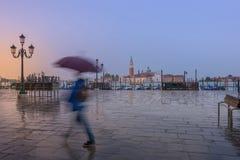 Apresúrese al hombre con la exposición larga del paraguas imagenes de archivo