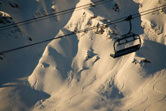 Empty ski lift in front of a mountain at sunset Royalty Free Stock Photos