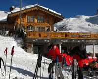 Apres ski in a mountain chalet bar, restaurant against panoramic view of Alps. Stock Image
