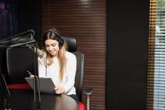 Apresentador de rádio fêmea latino-americano no estúdio imagem de stock