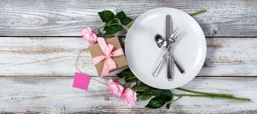 Apresente o ajuste com rosas e o presente cor-de-rosa na madeira branca rústica imagens de stock