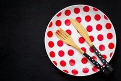 Apresente o ajuste com uma faca, uma forquilha e uma placa de bambu com às bolinhas imagens de stock royalty free