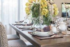Apresente o ajuste na sala dinning de madeira com o vaso da flor imagem de stock royalty free