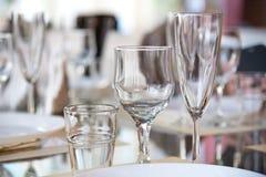 Apresente o ajuste no restaurante, incluindo vidros para o vinho, champanhe e conhaque, guardanapo e placas para convidados Fotos de Stock Royalty Free
