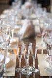 Apresente o ajuste no restaurante, incluindo vidros para o vinho, champanhe e conhaque, guardanapo e placas para convidados Foto de Stock