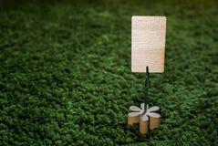 Apresente o suporte de nota do cartão do grampo com flor de madeira e um cartão vazio com copyspace no lado Fotos de Stock Royalty Free