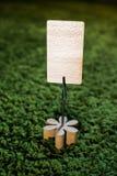 Apresente o suporte de nota do cartão do grampo com flor de madeira e um cartão vazio para copywriting no fundo verde Fotos de Stock