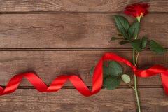 Apresente para o dia de Valentim do St - rosa do vermelho com a fita no copyspace de madeira escuro do fundo Imagens de Stock Royalty Free