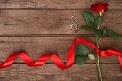 Apresente para o dia de Valentim do St - rosa do vermelho com a fita no copyspace de madeira escuro do fundo Fotografia de Stock Royalty Free