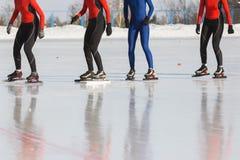 Apresse a competição de patinagem na pista de gelo no dia ensolarado do inverno - desportistas prontos para o começo Foto de Stock