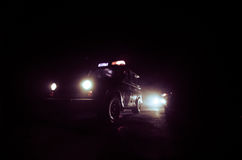 apresse a iluminação do carro de polícia na noite na estrada Carros de polícia na estrada que move-se com névoa Foco seletivo per Foto de Stock Royalty Free