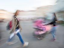 Apresuramiento y mujeres de la muchacha con un bebé en un cochecito foto de archivo libre de regalías