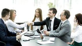 Apretón de manos agradable de socios comerciales en la mesa de negociación fotos de archivo libres de regalías