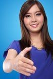 Apretón de manos asiático joven de la mujer, en fondo azul Fotos de archivo libres de regalías