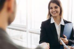 Apretón de manos atractivo sonriente de la empresaria con el hombre de negocios después de la charla agradable, buenas relaciones foto de archivo libre de regalías