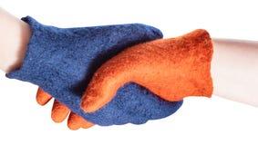 Apretón de manos de manos con guantes azules y anaranjadas fotografía de archivo