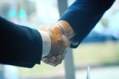 Apretón de manos confiado de socios comerciales en el fondo de la oficina Foto de archivo libre de regalías