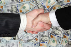 Apretón de manos de hombres de negocios en fondo de los billetes de banco Fotografía de archivo libre de regalías