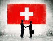 Apretón de manos de los hombres de negocios con la bandera de Suiza foto de archivo libre de regalías