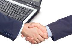 Apretón de manos del asunto con una computadora portátil Imagen de archivo libre de regalías