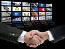 Apretón de manos del hombre de negocios sobre la pantalla de la perspectiva Imagen de archivo libre de regalías
