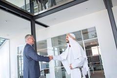 Apretón de manos del hombre de negocios con el socio árabe foto de archivo libre de regalías