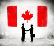 Apretón de manos del negocio con la bandera canadiense foto de archivo