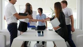 Apretón de manos del negocio entre los colaboradores en la reunión en oficina almacen de metraje de vídeo