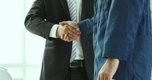 Apretón de manos del negocio junto en oficina moderna