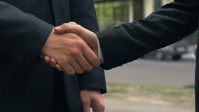 Apretón de manos de dos empresarios que colocan la oficina cercana, acuerdo, sociedad metrajes