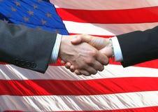 Apretón de manos e indicador americano Imágenes de archivo libres de regalías