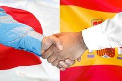 Apretón de manos en fondo de la bandera de España y de Japón imagen de archivo