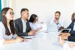 Apretón de manos en la reunión, documentos y gráficos del equipo del negocio de la diversidad en el escritorio Reunión del proyec imágenes de archivo libres de regalías