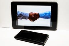 Apretón de manos en la tablilla con smartphone fotografía de archivo