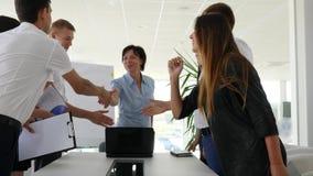 Apretón de manos entre los colaboradores acertados en la reunión de negocios en oficina almacen de video