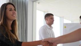 Apretón de manos entre los colaboradores en la reunión de negocios en oficina en ventanas grandes del fondo metrajes