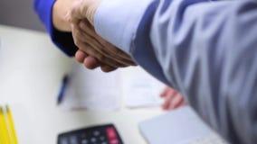 Apretón de manos entre un encargado del taller y un cliente almacen de metraje de vídeo