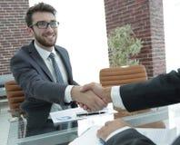Apretón de manos financiero de los socios después de firmar el contrato Imagen de archivo libre de regalías