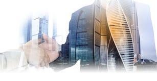 Apretón de manos de la foto de la exposición doble de la empresaria y hombre de negocios y rascacielos, edificios de oficinas El  foto de archivo